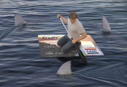 A man floating on a credit card paddling through an ocean of sharks